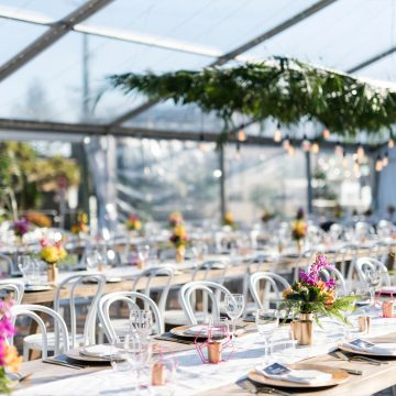 real-wedding-steph-ed-white-white-weddings-events-gold-coast-clear-marquee-long-wooden-tables-runner-colourful-flowers-hanging-palm-leaf-installation-bulb-lighting